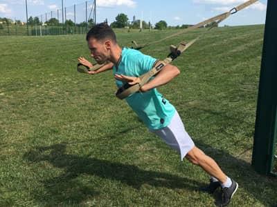 Renforcement musculaire avec le trx sur un coaching en extérieur